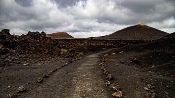 Schwarzes Lavagestein inmitten erloschener Vulkane auf Lanzarote